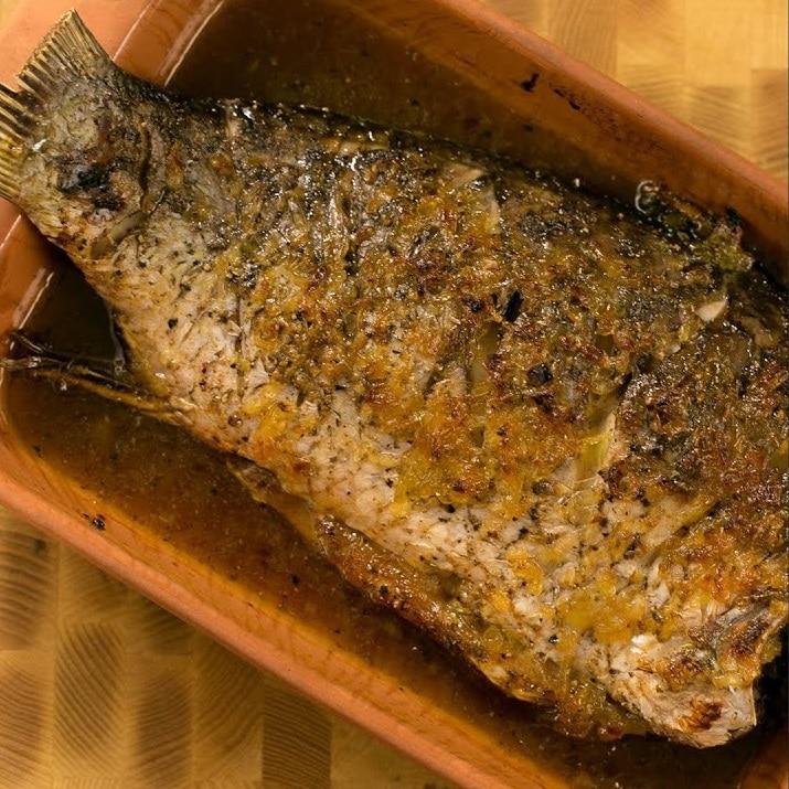 Kapr na medu pečený v misce s medem.