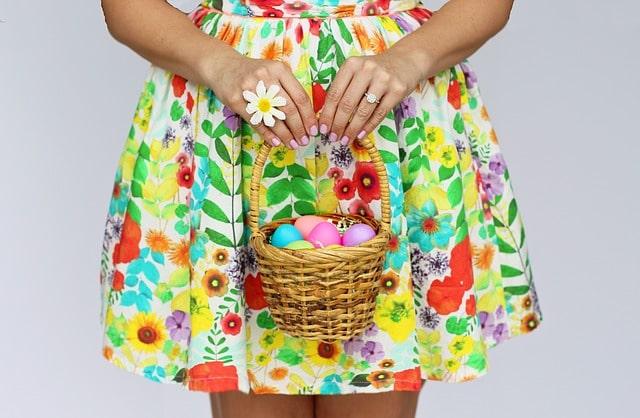Dívka držící košík velikonočních vajíček.