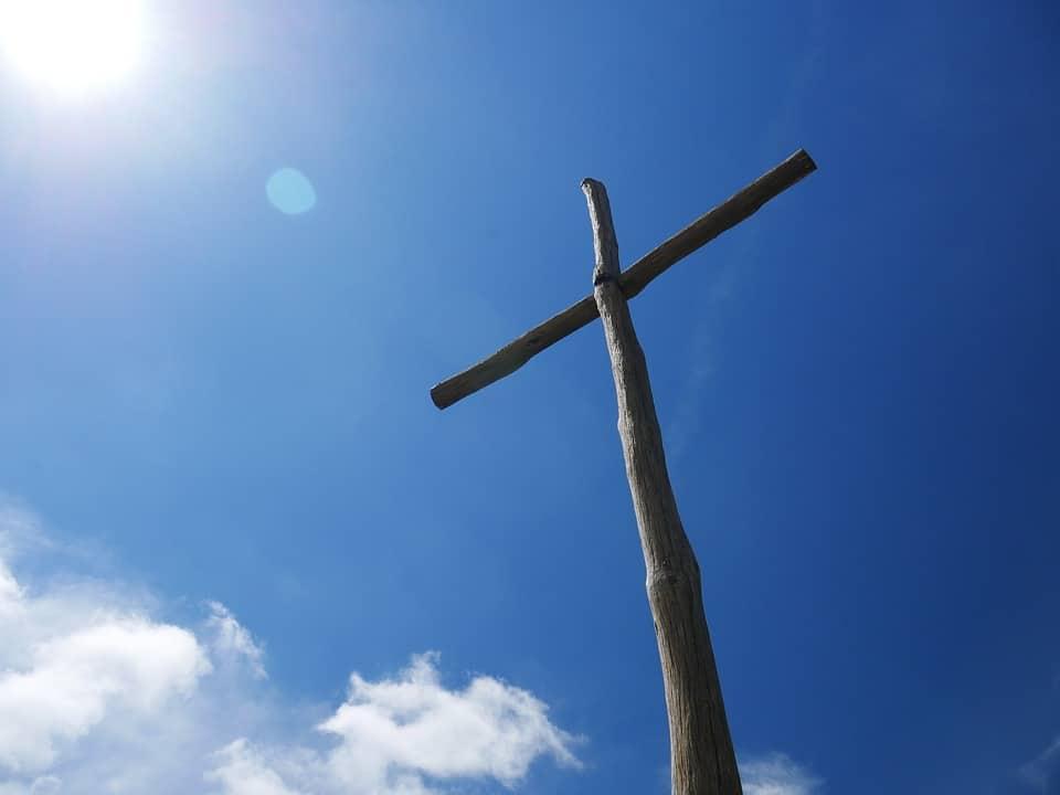 Křesťanský symbol kříže na modré obloze.