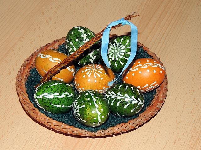 Malovaná velikonoční vajíčka v košíku s malou pomláskou.