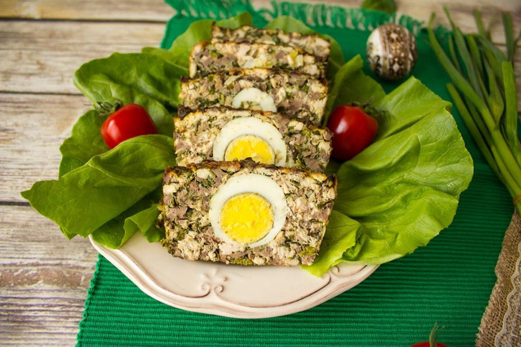Velikonoční sekaná s vajíčkem uprostřed na listovém salátu.