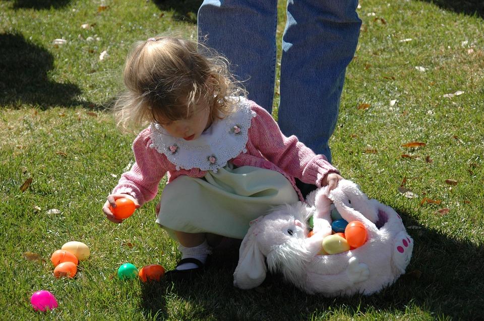 Dítě sbírá velikonoční vajíčka.